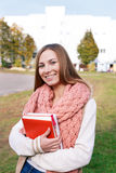 Student standing with books and looking at camera. In campus royalty free stock images