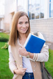 Student standing with books and looking at camera. Student standing with books in hands and looking at camera on the sunset royalty free stock image