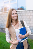Student standing with books in one hand and smiling. On the sunset royalty free stock image