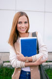 Student standing with books and smiling at camera. Student standing with books in her hands and smiling at camera stock photography