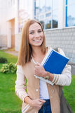 Student standing with books and smiling at camera. Student standing with books in her hands and smiling at camera on the sunset stock images