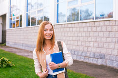 Student standing on building background and smiling. Student standing on building background with large windows royalty free stock photography