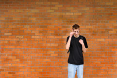 Student standing in front of brick wall. A tall white Caucasian young adult teenage male stands in front of a brick wall pulling down his glasses. Lots of room Royalty Free Stock Photo