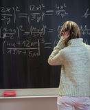 Student standing in front of a chalkboard Royalty Free Stock Images