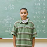 Student standing near blackboard Royalty Free Stock Images