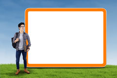 Student standing next to billboard Stock Images