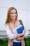 Student standing and smiling. Student standing with books in her hands and smiling at camera Stock Images