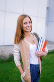 Student standing and smiling at camera. Student standing with books in her hands and smiling at camera royalty free stock photo