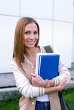 Student standing and smiling at camera. Student standing with books in her hands and smiling at camera royalty free stock image
