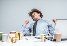 Student stretches from fatigue. Kneads the back at the workplace. Long working hours Stock Photos