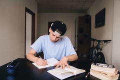 Student studies at home. Homework. A teen with a close look writes the text to his notebook. Student studies at home. The teen is carefully rewriting the tasks Stock Photos