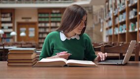 Student Studies in Library. Bright female student studying in huge library, prettty girl in green sweater and smart white blouse searching information on the stock video footage
