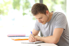 Student studying alone in a classroom. Single student studying taking notes alone in a classroom Royalty Free Stock Image