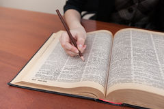 Student studying book. Student holding a pencil in his hand and is studying textbook Stock Images