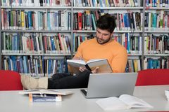 Student Studying at College. Handsome Male Student With Laptop and Books Working in a High School Library Royalty Free Stock Image