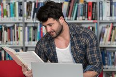 Student Studying at College. Handsome Man With Dark Hair Sitting at a Desk in the Library - Laptop and Organiser on the Table - Looking at the Screen a Concept Royalty Free Stock Photo