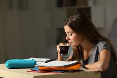 Student studying drinking coffee late hous. Side view portrait of a studious student studying drinking coffee late hous in the night at home royalty free stock photography