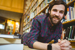 Student studying on floor in library wearing smart watch Royalty Free Stock Photos