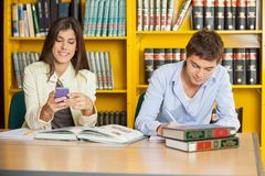 Student Studying While Friend Using Mobilephone In Stock Image