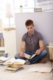 Student studying at home. Sitting on floor with books and notes, listening to music via headphones Stock Photo