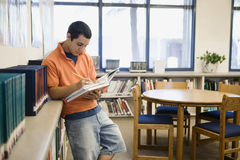 Student Studying in Library. Male high school student studying in library Stock Photos