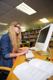 Student studying in the library with computer Royalty Free Stock Image
