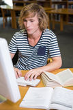 Student studying in the library with computer Stock Photography