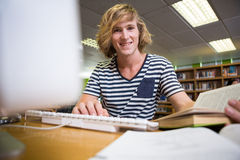 Student studying in the library with computer Royalty Free Stock Photography