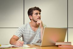 Composite image of student studying in the library with laptop. Student studying in the library with laptop against white tiling Royalty Free Stock Photo