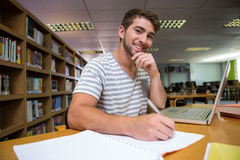 Student studying in the library with laptop Royalty Free Stock Image