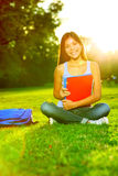 Student studying in park going back to school. At university college. Happy asian girl student sitting studying, writing and reading outside. Multi ethnic royalty free stock image