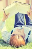 Student studying in park reading a book Stock Photo