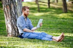 Student studying in park. Smart student studying outdoors in green park Stock Images