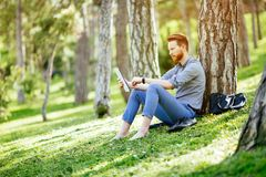Student studying in park. Smart student studying outdoors in green park Stock Photos