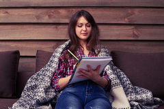 Student studying while sitting on the sofa in a cosy atmosphere Stock Photo