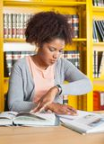 Student Studying At Table In University Library. Female college student studying at table in university library stock photography