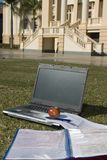 Student Stuff. Laptop and lecture notes in front of a college building Stock Photography