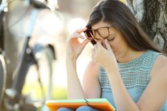 Student suffering eyestrain while is studying. Single student wearing eyeglasses suffering eyestrain while is studying in a park royalty free stock photo