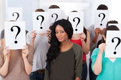 Student surrounded by classmates holding question mark signs Royalty Free Stock Photo