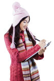 Student with sweater writes on clipboard Stock Images
