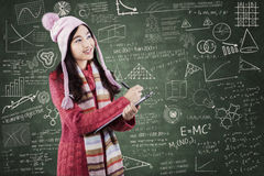 Student in sweater writes on lipboard at class Royalty Free Stock Image