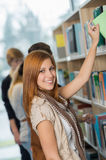 Student taking book from bookshelf in library Stock Photos