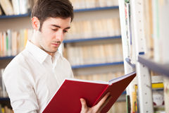 Student taking a book in a library Stock Images