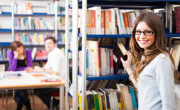 Student taking a book in a library Royalty Free Stock Images