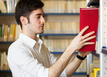 Student taking a book in a library Royalty Free Stock Photo