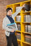 Student Taking Book From Shelf In College Library. Portrait of confident male student taking book from shelf in college library Royalty Free Stock Photos
