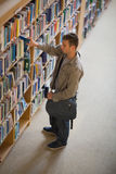 Student taking a book from shelf in library Royalty Free Stock Photos