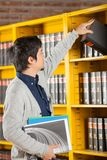 Student Taking Book From Shelf In University. Young male student taking book from shelf in university library Royalty Free Stock Images