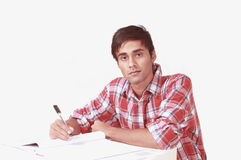 Student taking notes. Serious young male student writing notes in a notes folder Royalty Free Stock Images