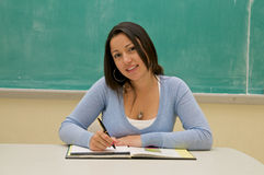 Student taking notes in the classroom blackboard Stock Photo